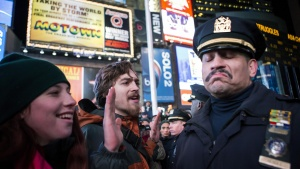 A NYPD policeman reacts next to people protesting against the Staten Island death of Eric Garner during an arrest in July, in midtown Manhattan, New York December 3, 2014.