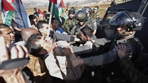 Palestinian minister Ziad Abu Ein (L) scuffles with an Israeli border policeman near the West Bank city of Ramallah, December 10, 2014. Ziad Abu Ein, 55, a minister without portfolio, died shortly after an Israeli border policeman shoved and grabbed him by the throat during a protest in the West Bank. It was not clear what caused his death.