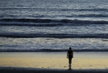 A woman walks out of the ocean following a swim past sunset at Moon Light Beach in Encinitas, California October 28, 2014.    REUTERS/Mike Blake