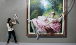 A student pose in front of a 3D painting during class field trip at the Art In Island Museum in Quezon City, metro Manila March 6, 2015. REUTERS/Romeo Ranoco