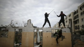 Palestinian youths fight with swords as they demonstrate their ninja-style skills for the photographer at the ruins of a house, that was destroyed in 2014 war, in the northern Gaza Strip January 29, 2016.  REUTERS/Mohammed Salem