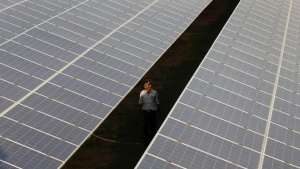 A private security guard walks between rows of photovoltaic solar panels inside a solar power plant at Raisan village near Gandhinagar, in Gujarat, February 11, 2014. REUTERS/Amit Dave/Files