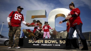 A family poses on a Super Bowl logo outside Levi's Stadium before NFL Super Bowl 50 in Santa Clara, California, United States, February 6, 2016. REUTERS/Lucy Nicholson