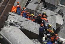 Rescuers carry a 20-year-old male survivor, identified by Taiwan media as Huang Kuang-wei, out from the site where a 17-storey apartment building collapsed after an earthquake hit Tainan, southern Taiwan February 7, 2016. REUTERS/Tyrone Siu