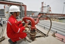 A fireman holds a water supply nozzle while petroleum products are transported on a vessel from the Vadinar refinery, operated by Essar Oil Ltd., (EOL) on jetty off Essar ports in Gujarat June 6, 2012. REUTERS/Amit Dave/Files