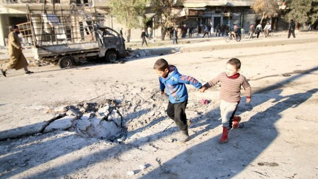 Boys run near a hole in the ground after airstrikes by pro-Syrian government forces in the rebel held al-Sakhour neighborhood of Aleppo, Syria February 8, 2016. REUTERS/Abdalrhman Ismail