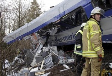 Rescuers stand in front of a carriage at the site of the two crashed trains near Bad Aibling in southwestern Germany, February 9, 2016. REUTERS/Josef Reisner