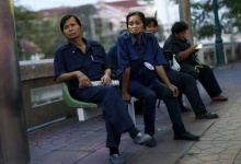Pranom Chartyothin, a 72-year-old bus conductor, (2nd L) waits with colleagues for a bus in downtown Bangkok, Thailand, February 3, 2016. REUTERS/Jorge Silva