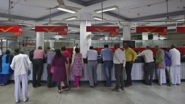 Retail depositors and their agents stand at the counters of an Indian post office in New Delhi, October 9, 2015. REUTERS/Anindito Mukherjee/Files