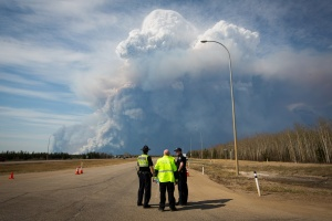 Officers look on as smoke from Fort McMurray's raging wildfires billow into the air after their city was evacuated, May 4, 2016. REUTERS/Topher Seguin