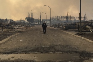 A Mountie surveys the damage on a street in Fort McMurray, Alberta, Canada in this twitter image posted on May 5, 2016. Courtesy RCMP Alberta/Handout via REUTERS