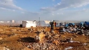 A fireman douses burnt tents at a camp for internally displaced people near Sarmada in Syria's Idlib province in this undated still image taken from video on May 6, 2016.  Social Media