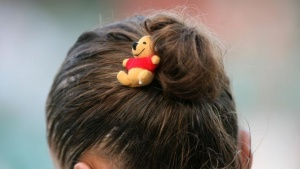 A girl wears a Winnie-the-Pooh teddy bear in her hair in London June 30, 2006.    REUTERS/Alessia Pierdomenico/Files