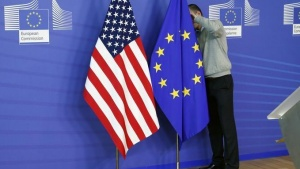 A worker adjusts European Union and U.S. flags at the start of the 2nd round of EU-US trade negotiations for Transatlantic Trade and Investment Partnership at the EU Commission headquarters in Brussels November 11, 2013. REUTERS/Francois Lenoir/Files