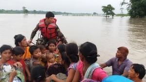 An army officer assists flood victims in Jhapa, Nepal, July 24, 2016.  Picture taken July 24, 2016. Nepalese Army/Handout via REUTERS