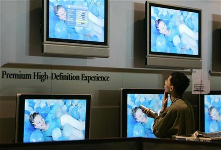 A technician looks at television screens in Las Vegas, January 3, 2006. REUTERS/Rick Wilking