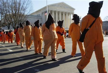 Protesters dressed as prisoners from the U.S. detention facility at Guantanamo Bay march past the U.S. Supreme Court building in Washington, January 11, 2007. An appeals court on Tuesday upheld the part of a tough anti-terrorism law signed by President George W. Bush that took away the right of Guantanamo prisoners to challenge their detention before U.S. federal judges. REUTERS/Jonathan Ernst