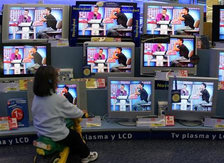 A young girl watches TV screens at a store in Santander, Spain in this November 21, 2005 file photo. Watching television disrupts children's' normal response to food -- they will eat more while they're sitting in front of the tube, whether or not they're really hungry. REUTERS/Victor Fraile