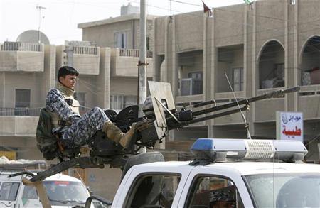 An Iraqi soldier mans a machine gun mounted on a vehicle at a checkpoint in Baghdad's Sadr City, February 25, 2007. REUTERS/Kareem Raheem
