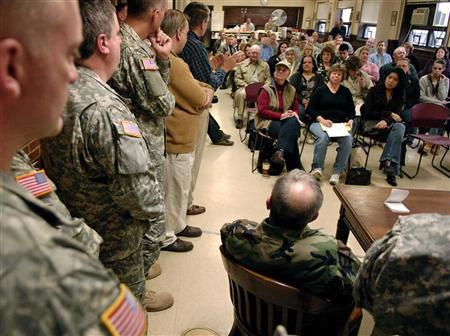 Military officials answer questions at the New Jersey National Guard armory in Bordentown, January 13, 2007, as family members of soldiers deployed learned details about the extension to their deployment orders. Ten percent of the 130,000 U.S. troops in Iraq are Guard members. REUTERS/Chip East