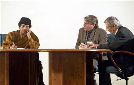 Libyan leader Muammar Gaddafi (L) listens during his debate on democracy with British sociologist Anthony Giddens (R) and U.S. political scientist Benjamin Barber (2nd R) in the desert in Sebha March 2, 2007, in a move apparently designed to further the resumption of international ties following years of isolation. Gaddafi, ever the political showman, has chosen the talk show as a new way of sending a message to the West: Economic reform will help Libya, but political change is not needed. REUTERS/Louafi Larbi