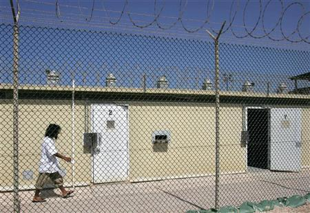In this photo reviewed by US military officials, a detainee, whose name, nationality, and facial identification are not permitted, walks past cell doors within the grounds of the Camp Delta 4 military-run prison, at the Guantanamo Bay U.S. Naval Base, Cuba June 27, 2006. U.S. military officials will start hearings on Friday for 14 prisoners transferred to Guantanamo Bay from secret CIA jails, including the alleged mastermind of the September 11 attacks on the United States. REUTERS/Brennan Linsley/Pool