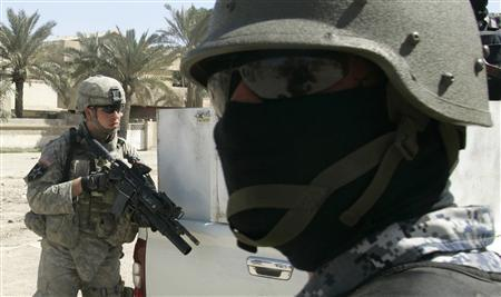 A U.S. soldier (L) from Delta company 2/325, 82nd Airborne and an Iraqi national police officer conduct a joint patrol in Baghdad's Sadr City March 11, 2007. REUTERS/Fabrizio Bensch