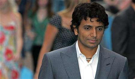 Director M. Night Shyamalan poses as he arrives at the European Premiere of his film ''Lady in the Water'' at the Vue cinema in London's Leicester Square, August 8, 2006 file photo. Shyamalan will return to his provocative, dark Hitchcockian style with ''The Happening'', a thriller about a natural calamity that threatens to wipe out humanity. REUTERS/Luke MacGregor