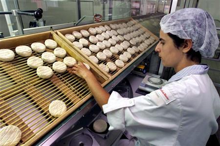 A cheese factory employee in a file photo. Scientists have found a way to ensure starter cultures used to make cheese can ward off attacks from bacteria-eating viruses -- a finding that could mean the difference between a great Gouda and wasted milk. REUTERS/File