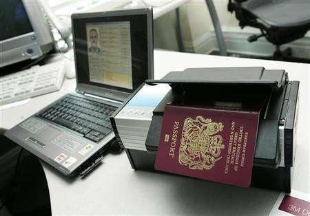 A new British biometric passport is shown atop a special reader can take the holder's information off an embedded security chip, during a showing for the press at the British Embassy in Washington, in this October 24, 2005 file photo. Police have charged 15 people after raids on illegal passport factories and suppliers, Scotland Yard said on Friday. REUTERS/Jason Reed