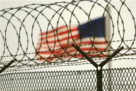 In this photo reviewed by US military officials, an American flag waves within the razor wire-lined compound of Camp Delta prison, at the Guantanamo Bay U.S. Naval Base, Cuba June 27, 2006. The U.S. military prison at Guantanamo Bay will likely remain open for the rest of George W. Bush's presidency because it will take time to conduct the legal proceedings of the detainees there, the White House said on Friday. REUTERS/Brennan Linsley/Pool