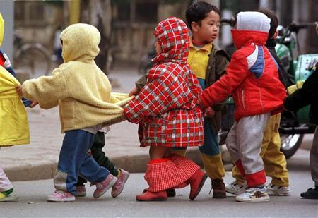 Toddlers form a human chain to cross a busy intersection on her way to kindergarten in Hanoi in a file photo. Some effects of poor quality day care last until age 10 or 11, but very few, and good parenting is probably more important, U.S. government researchers reported on Monday. REUTERS/Dylan Martinez