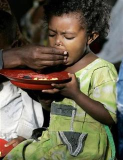 An Ethiopian child, whose roots are said to trace back to Judaism, is fed by her mother at a feeding centre in Gondor, Ethiopia March 8, 2007, while awaiting immigration to Israel. Thousands of Ethiopians who say their Jewish roots entitle them to live in Israel are stuck in a squalid camp in Ethiopia, their dream of a promised land fading as Israel scrutinises their family ties. Picture taken March 8, 2007. To match feature ETHIOPIA-JEWS/ REUTERS/Eliana Aponte