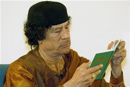 Libyan leader Muammar Gaddafi reads a green book during his debate on democracy with two Western scholars in the desert in Sebha March 2, 2007. Gaddafi said on Friday that it was a mistake to believe that Christianity was a universal faith alongside Islam. REUTERS/Louafi Larbi