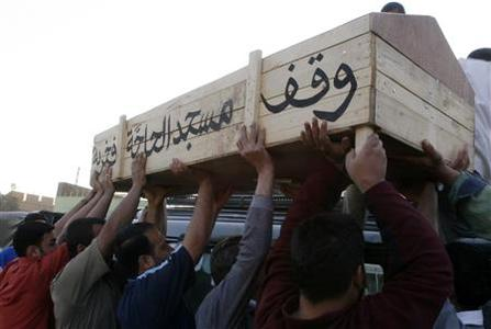 Men place a coffin of a bomb attack victim on a top of a vehicle after claiming his body from a hospital morgue in Baghdad March 30, 2007. REUTERS/Kareem Raheem