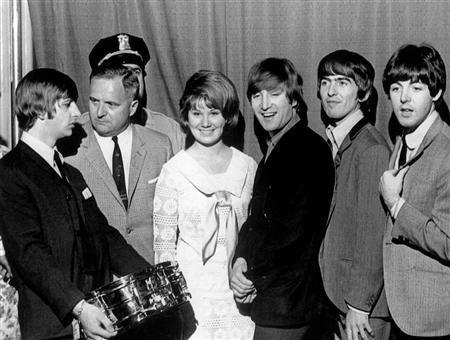 Ringo holds a gold-plated drum as the other Beatles look on in a 1964 ceremony in Chicago. Apple Inc. and EMI Group will reveal a ground-breaking deal on Monday for Apple to sell the music label's songs free from copy protection limits, the Wall Street Journal reported on Sunday. REUTERS/PRNewsFoto