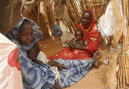 Internally displaced Sudanese women sit inside their make-shift house in their camp near El-Fasher, capital of the north Darfur region, March 25, 2007. REUTERS/Michael Kamber