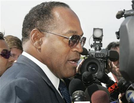 Former NFL star and actor O.J. Simpson talks with reporters as he arrives for the funeral of attorney Johnnie Cochran in Los Angeles, April 6, 2005. A court-ordered auction of the rights to O.J. Simpson's quasi-confessional book ''If I Did It'' was canceled because the former football star's surrogate company has declared bankruptcy, an attorney for the father of murder victim Ron Goldman said on Monday. REUTERS/Fred Prouser