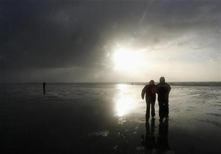 The sun breaks through storm clouds as a couple walks along the shore in St. Peter Ording on the North Sea coast January 18, 2007. Business is booming for a Berlin entrepreneur's unique service -- delivering break-up messages for a fee. REUTERS/Christian Charisius