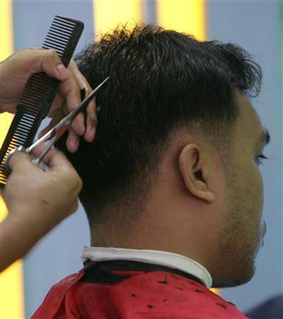 A man gets a haircut inside a hairdressing salon in Quezon city, suburban Manila, in this August 25, 2006 file photo. Iranian police have warned barbers against offering Western-style hair cuts or plucking the eyebrows of their male customers, Iranian media said on Sunday. REUTERS/Romeo Ranoco