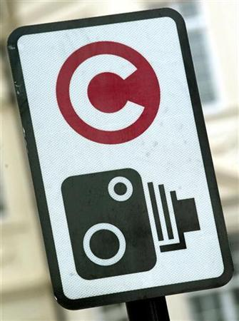 A traffic sign with a ''C'' symbol indicating the start of the congestion charging zone and a camera are seen in central London, February 16, 2003. Spies in the sky may track motorists in Britain within a decade if the government goes ahead with controversial plans to introduce road user charging schemes, scientists said on Tuesday. REUTERS/Stephen Hird