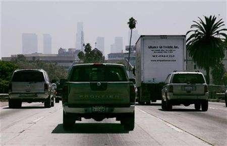Cars and trucks travel on a freeway in Los Angeles, August 31, 2006 with the skyline of Los Angeles barely visible in background. With pressure growing on the government to regulate greenhouse gas emissions blamed for global warming, 31 U.S. states will start a registry next year to track those emissions with an eye toward reducing them. REUTERS/Fred Prouser