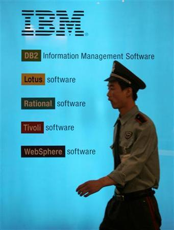 A security guard walks past an IBM poster at China International Software Exhibition in Beijing, in this June 2, 2006 file photo. IBM is starting a $1 billion-a-year investment program aimed at doubling the energy efficiency of its data centers and those of its corporate customers, the New York Times reported on its Web site on Thursday.REUTERS/Jason Lee