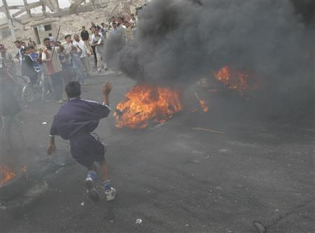 A protester chants slogans near burning tyres during a demonstration in Basra, 550 km (340 miles) south of Baghdad May 16, 2007. Iraq's government has lost control of vast areas to powerful local factions and the country is on the verge of collapse and fragmentation, a leading British think-tank said on Thursday. REUTERS/Atef Hassan