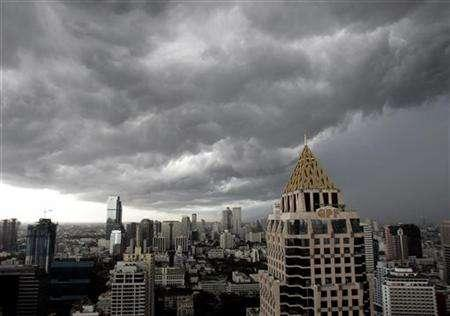 Dark rain clouds hang over Bangkok skyscrapers, in this July 12, 2006 file photo. La Nina, a weather phenomenon characterized by incessant rainfall, storms and flooding in most parts of Asia, may be emerging again this year, and farmers may have to brace themselves for a ''wet'' dry season. REUTERS/Chaiwat Subprasom