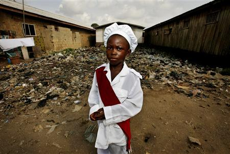 Stephen Shedara, wearing his Sunday dress, stops near a rubbish pile on his way to a Pentecostal church in the Ilaje slum in Nigeria's commercial capital Lagos April 22, 2007. Despite some progress, sub-Saharan Africa is behind schedule on all its U.N. Millennium Development Goals, which include halving extreme poverty, halfway towards their target date, the world body reported on Wednesday. REUTERS/Finbarr O'Reilly