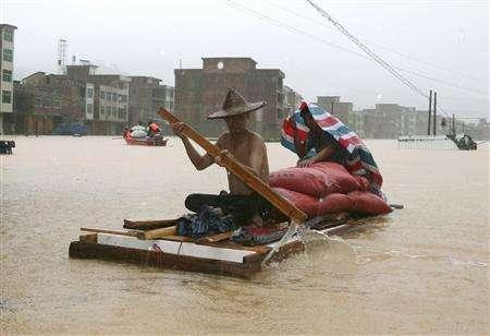 A man paddles through a flooded street during a rainy day in Meizhou, south China's Guangdong province, June 10, 2007. Storm floods in southern China have destroyed nearly 50,000 homes, killed at least 66 people and forced over 500,000 others to flee the area, Xinhua news agency reported on Sunday, citing the Ministry of Civil Affairs. REUTERS/China Daily