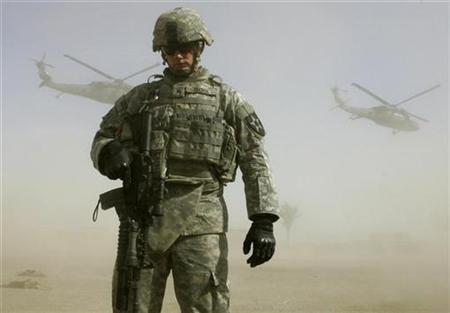 A U.S. soldier shields himself from dust as Blackhawk helicopters take off south of Baghdad, March 5, 2007. Global military spending rose 3.5 percent last year to $1.2 trillion as U.S. costs for operations in Iraq and Afghanistan mounted, a European research body said on Monday in an annual study. REUTERS/Fabrizio Bensch