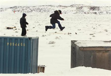 An Inuit boy jumps from a ship container to a shed in the Canadian Arctic town of Iqaluit in a file photo. Even Canada's thinly populated Arctic regions can play a role in curbing global warming, by reducing soot from dirty, old cooking stoves which are blackening snow and making it melt faster. It's one problem on a list of many outlined by researchers at the universities of California and Colorado. REUTERS/File