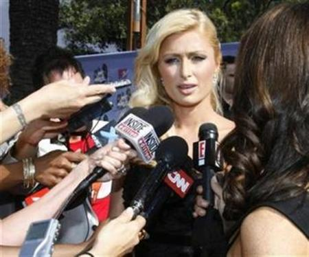 Paris Hilton talks to reporters as she arrives at the 2007 MTV Movie Awards in Los Angeles, California June 3, 2007. Hilton appeared to be a celebrity without a spotlight on Friday after two major U.S. television networks snubbed the hotel heiress they initially fought over for a first post-jail interview. REUTERS/Fred Prouser